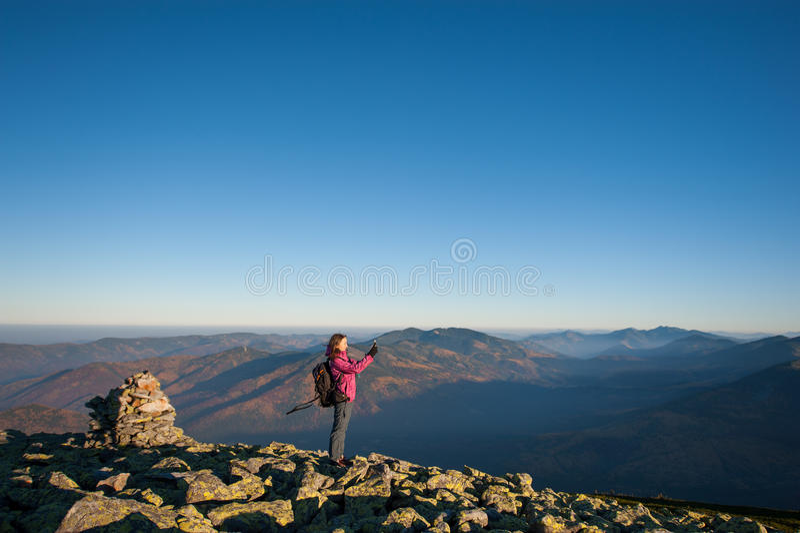 Menina bonita que toma a imagem com seu smartphone nas montanhas imagens de stock royalty free
