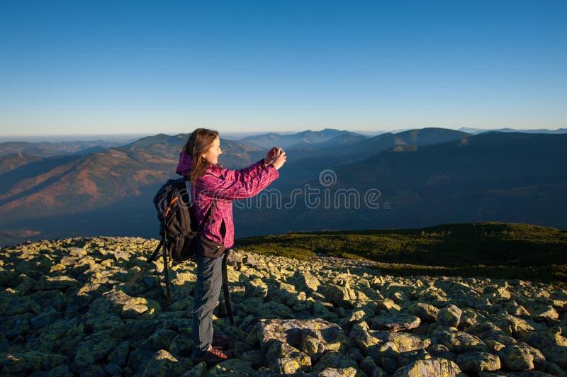 Menina bonita que toma a imagem com seu smartphone nas montanhas fotos de stock