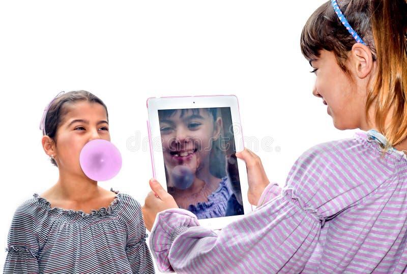 Menina bonita que toma imagens com a tabuleta de sua irmã imagens de stock