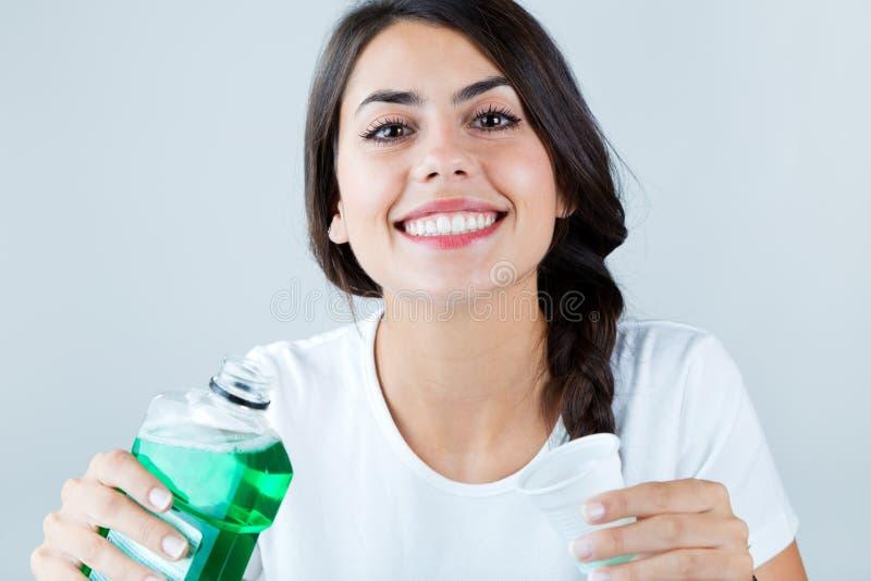 Menina bonita que usa o colutório Isolado no branco imagem de stock