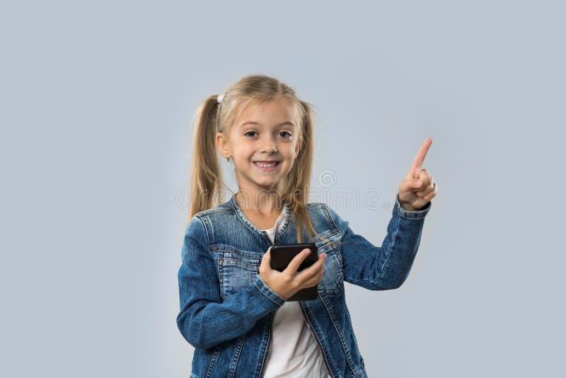 Menina bonita que usa o dedo de sorriso feliz do ponto do telefone esperto da pilha para copiar o espaço isolado imagem de stock royalty free