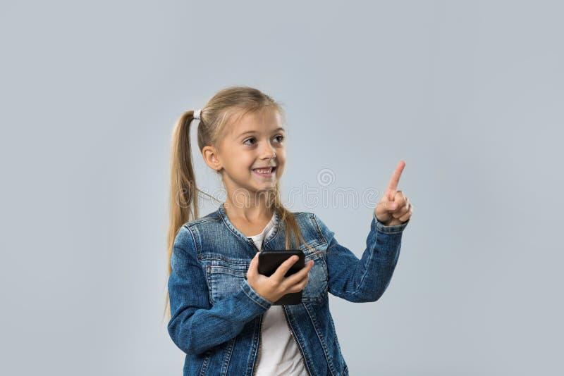 Menina bonita que usa o dedo de sorriso feliz do ponto do telefone esperto da pilha para copiar o espaço isolado imagens de stock royalty free