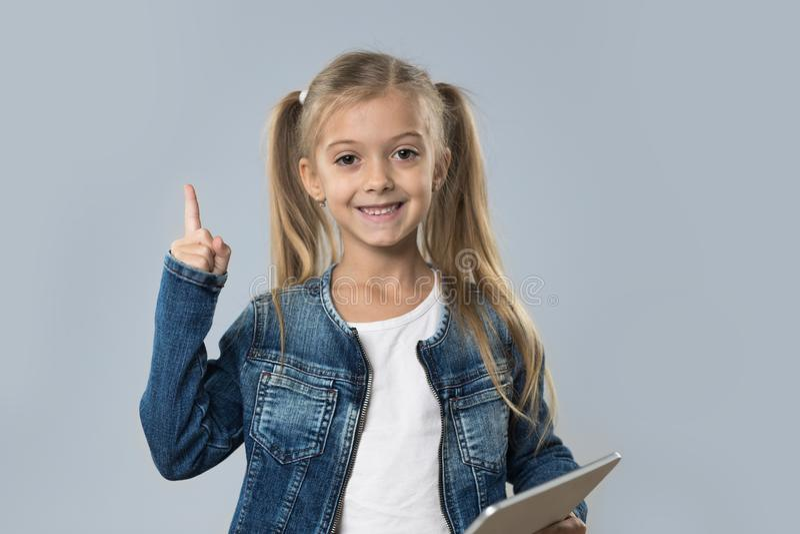 Menina bonita que usa o dedo do ponto do tablet pc até o sorriso feliz do espaço da cópia isolado imagem de stock