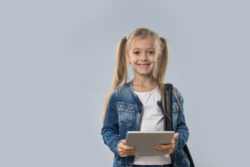 Menina bonita que usa o revestimento de sorriso feliz das calças de brim do desgaste do tablet pc isolado foto de stock royalty free