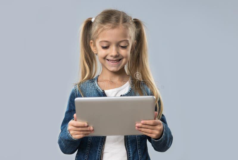 Menina bonita que usa o revestimento de sorriso feliz das calças de brim do desgaste do tablet pc isolado imagens de stock