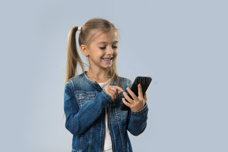 Menina bonita que usa o revestimento de sorriso feliz das calças de brim do desgaste do telefone esperto da pilha isolado foto de stock