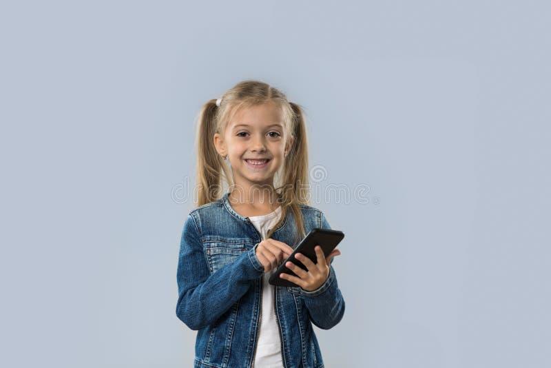 Menina bonita que usa o revestimento de sorriso feliz das calças de brim do desgaste do telefone esperto da pilha isolado imagem de stock royalty free