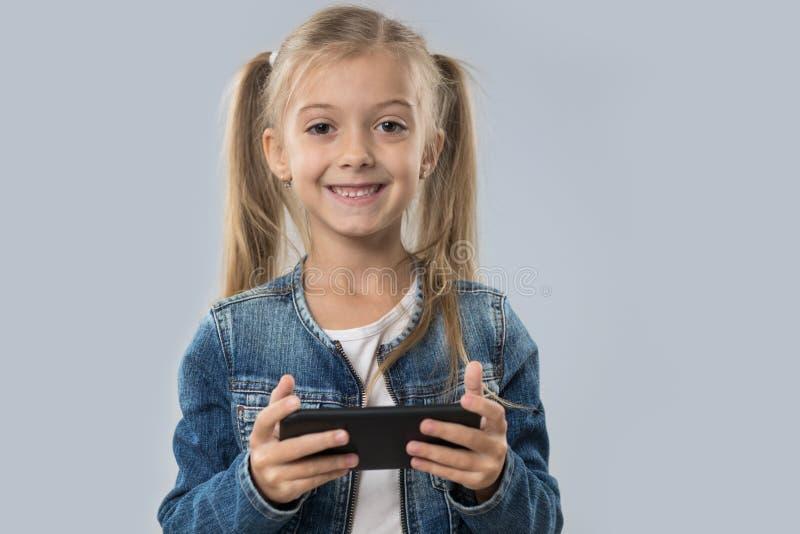 Menina bonita que usa o revestimento de sorriso feliz das calças de brim do desgaste do telefone esperto da pilha isolado imagens de stock