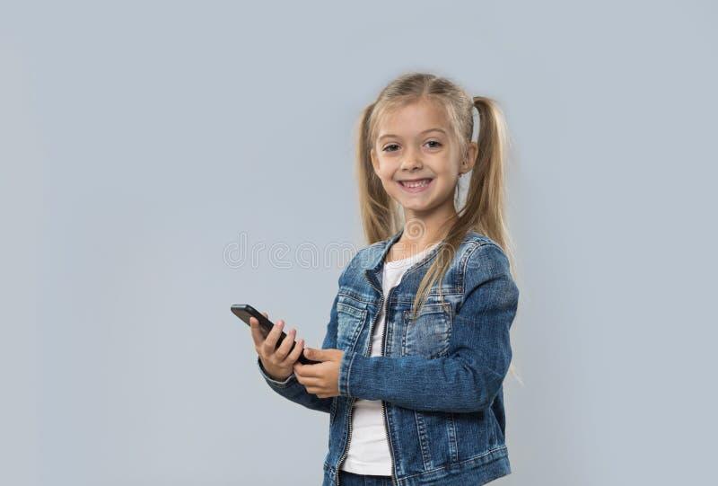 Menina bonita que usa o revestimento de sorriso feliz das calças de brim do desgaste do telefone esperto da pilha isolado foto de stock royalty free