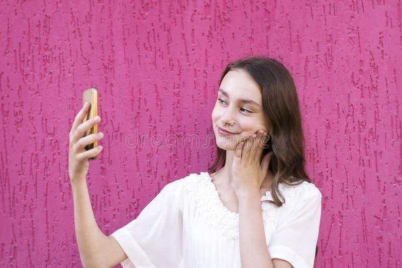 Menina bonita que usa o telefone celular para o divertimento foto de stock royalty free