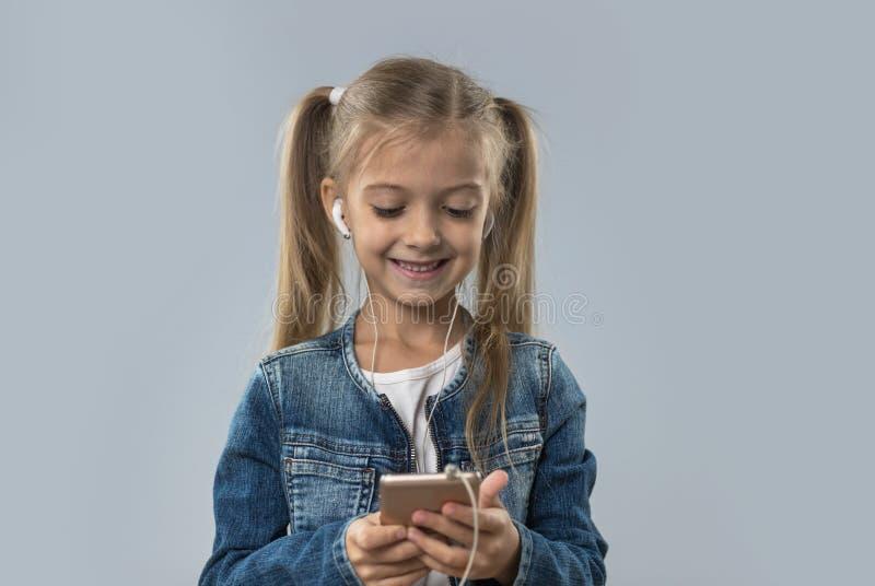 A menina bonita que usa o telefone esperto da pilha escuta sorriso feliz dos fones de ouvido do desgaste da música isolado fotos de stock