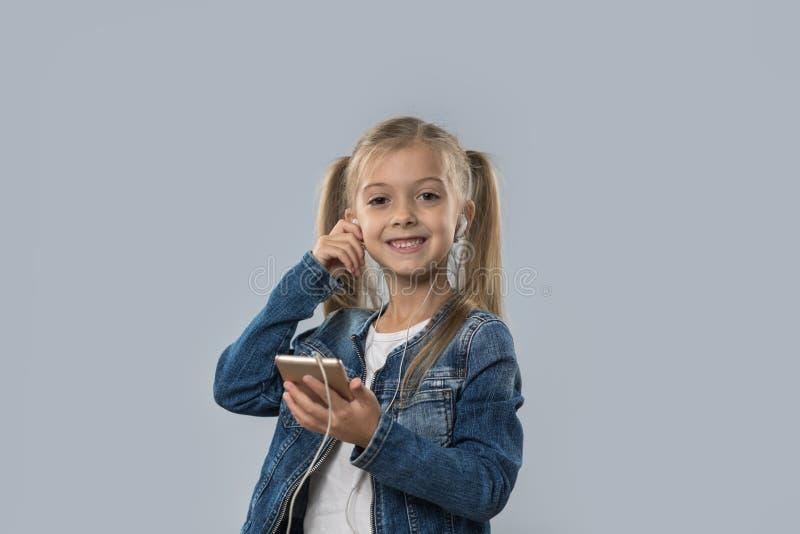 A menina bonita que usa o telefone esperto da pilha escuta sorriso feliz dos fones de ouvido do desgaste da música isolado fotos de stock royalty free
