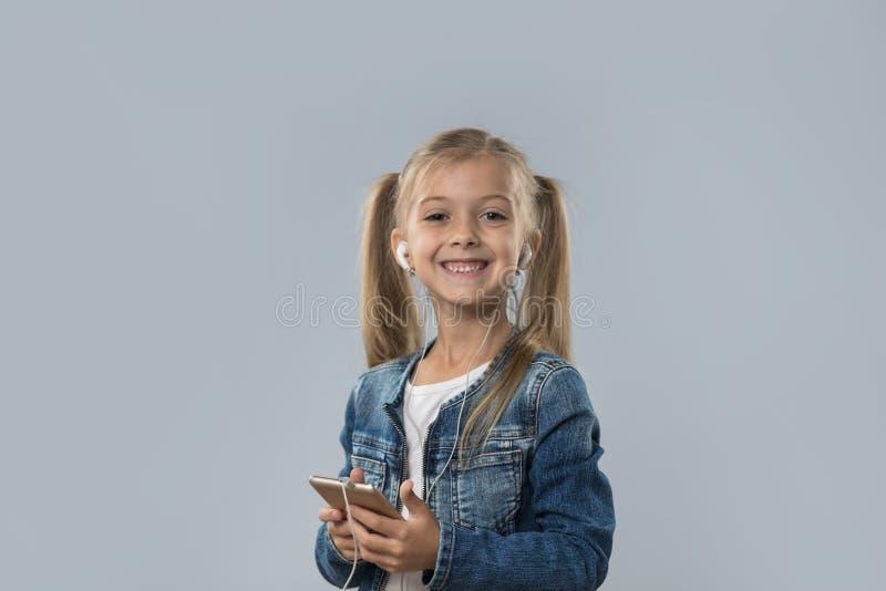 A menina bonita que usa o telefone esperto da pilha escuta sorriso feliz dos fones de ouvido do desgaste da música isolado fotografia de stock