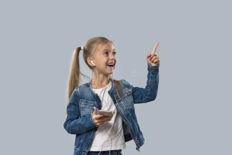 A menina bonita que usa o telefone esperto escuta olhar de sorriso feliz dos fones de ouvido do desgaste da música para copiar o  imagem de stock