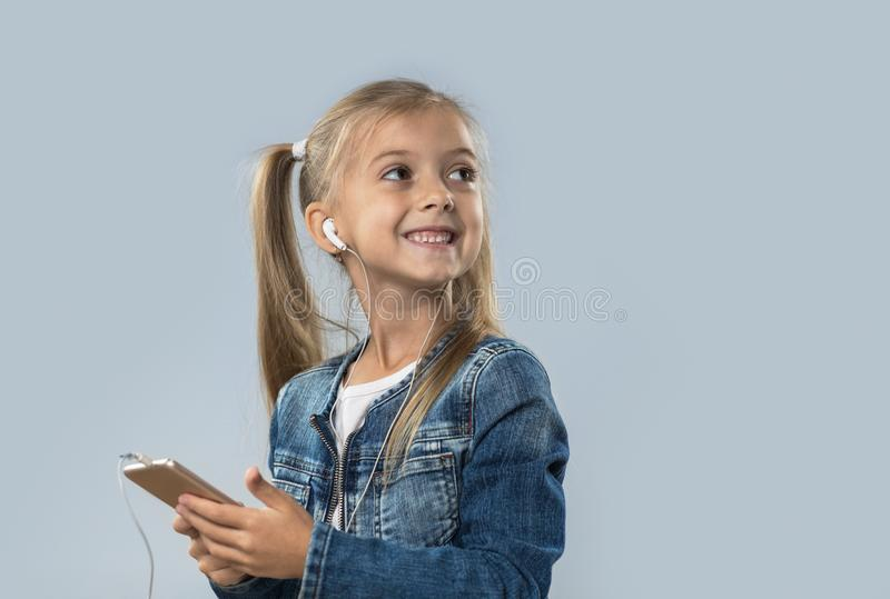 A menina bonita que usa o telefone esperto escuta olhar de sorriso feliz dos fones de ouvido do desgaste da música para copiar o  fotos de stock