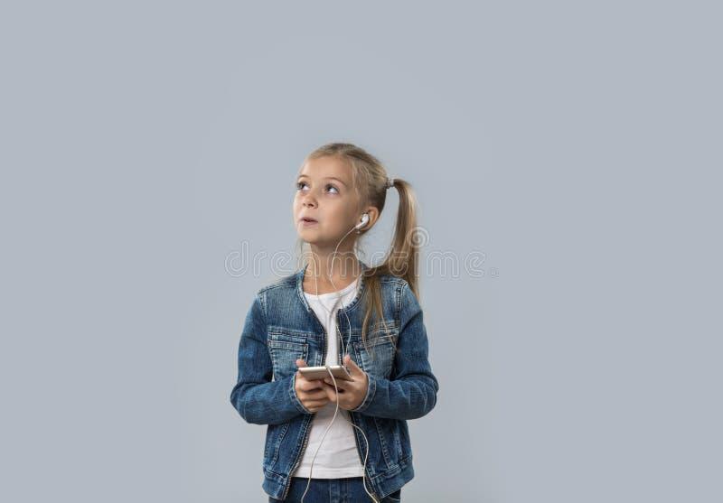 A menina bonita que usa o telefone esperto escuta olhar de sorriso feliz dos fones de ouvido do desgaste da música para copiar o  imagens de stock royalty free