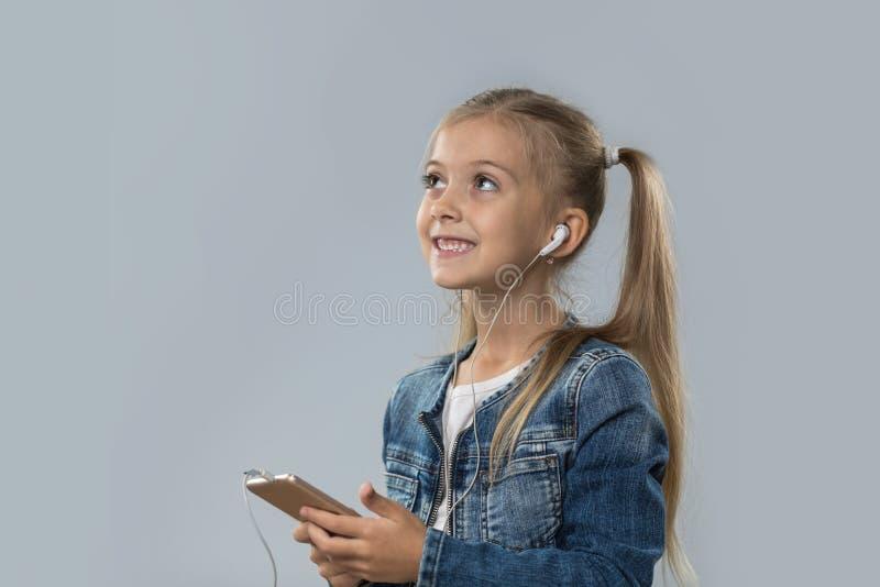 A menina bonita que usa o telefone esperto escuta olhar de sorriso feliz dos fones de ouvido do desgaste da música para copiar o  fotografia de stock royalty free