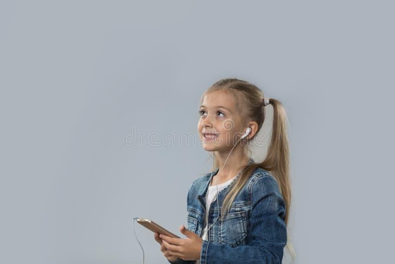 A menina bonita que usa o telefone esperto escuta olhar de sorriso feliz dos fones de ouvido do desgaste da música para copiar o  imagens de stock