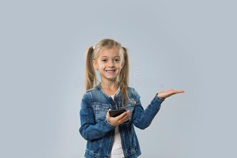Menina bonita que usa a palma aberta de sorriso feliz do telefone esperto da pilha ao espaço da cópia isolado fotos de stock royalty free