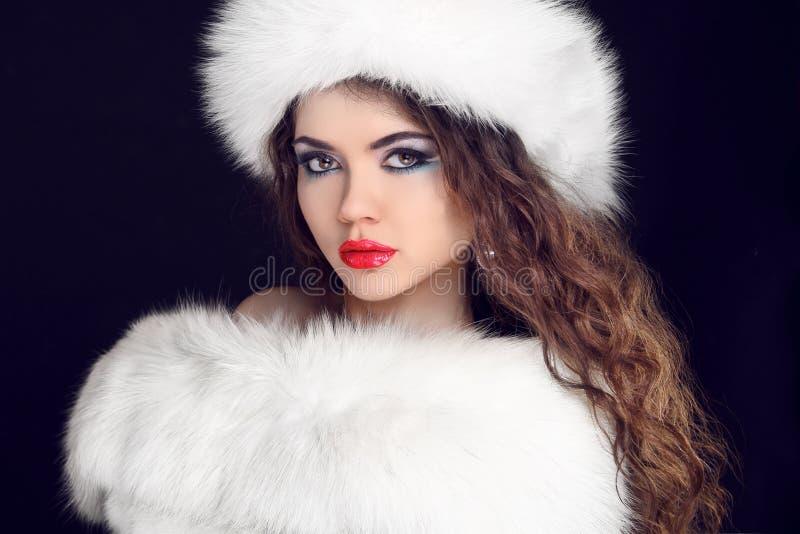 Menina bonita que veste no casaco de pele branco e no chapéu peludo. inverno W imagens de stock