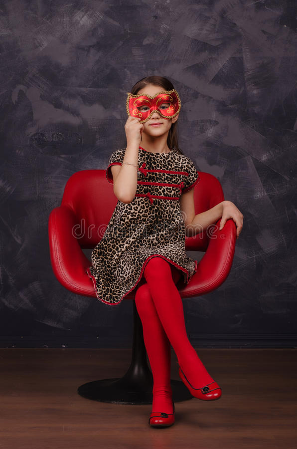 Menina bonita que veste o vestido bonito que senta-se na poltrona vermelha Está vestindo a máscara vermelha do carnaval do disfar imagens de stock royalty free