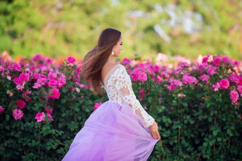 Menina bonita que veste o vestido elegante que levanta perto das flores coloridas Trabalho de arte da mulher rom?ntica fotografia de stock