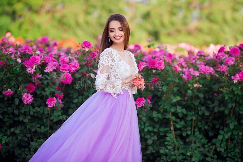 Menina bonita que veste o vestido elegante que levanta perto das flores coloridas Trabalho de arte da mulher rom?ntica fotografia de stock royalty free