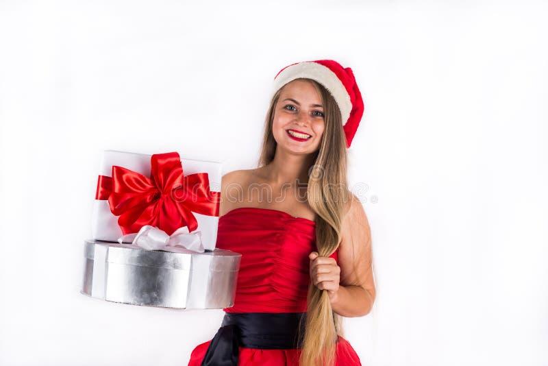 Menina bonita que veste o vestido vermelho que mantém a caixa de presente atual isolada no branco fotografia de stock
