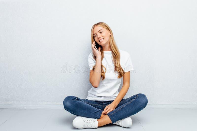Menina bonita que veste um t-shirt branco, falando no telefone, sentando-se no assoalho em um fundo cinzento fotos de stock royalty free