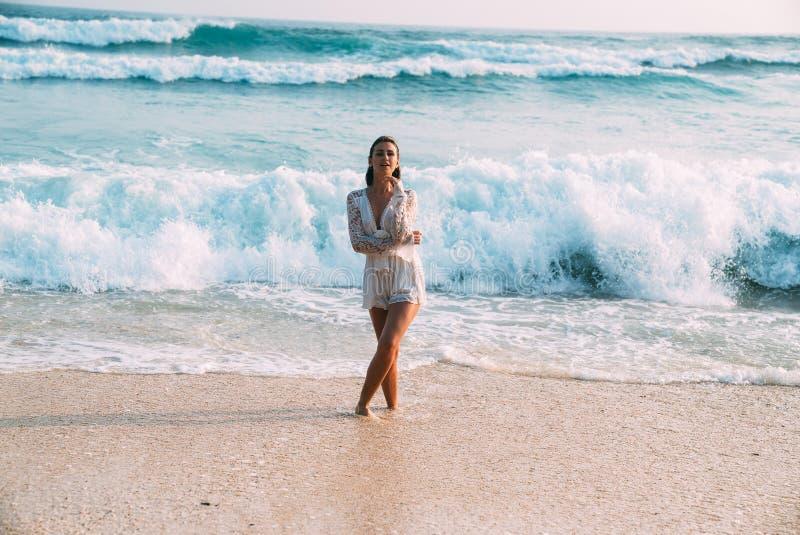 A menina bonita sedutor em uma praia elegante bordou suportes do vestido na praia, contra um fundo da elevação fotos de stock