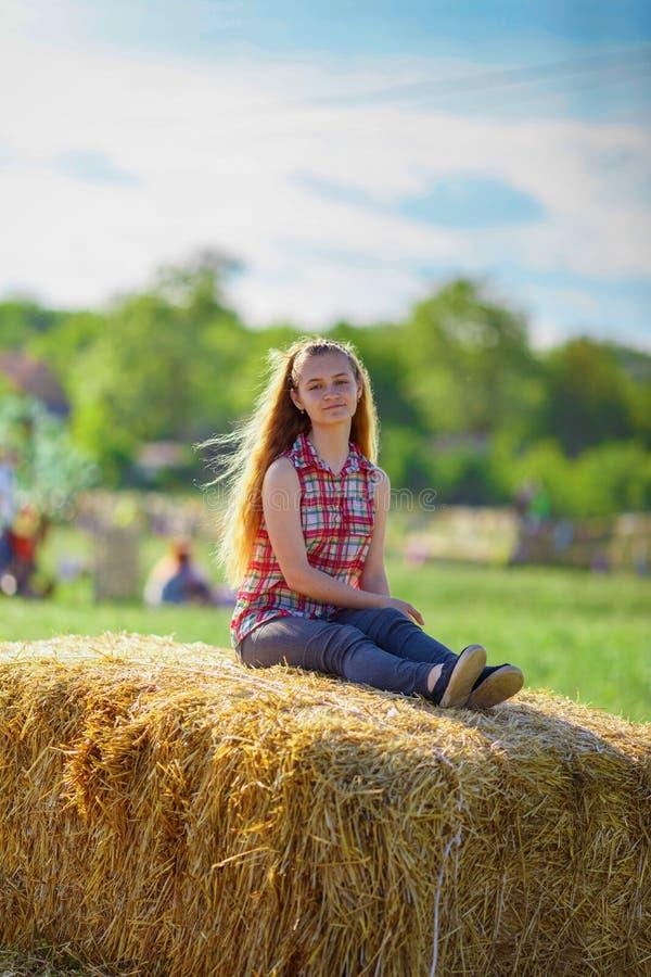 A menina bonita senta-se em um monte de feno fotos de stock royalty free