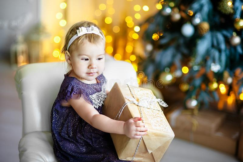 A menina bonita, senta-se em um sofá com um presente nas mãos, em um interior festivo Um grupo de faíscas brilhantes na imagens de stock royalty free