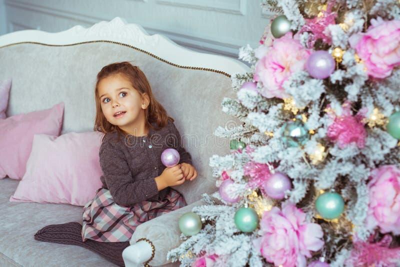 A menina bonita senta-se em um sofá perto da árvore de Natal e olha-se acima fotos de stock royalty free