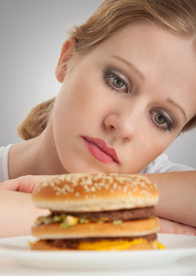 A menina bonita senta-se em uma dieta, triste e no Hamburger fotos de stock royalty free