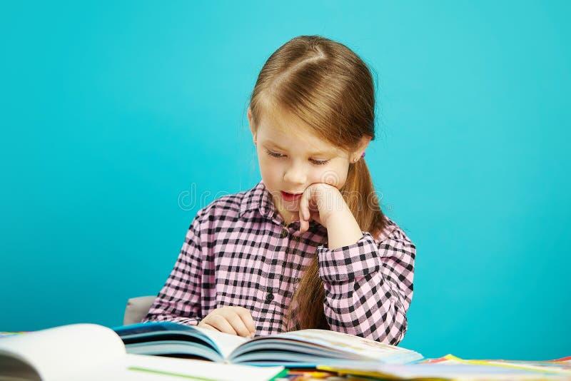 A menina bonita senta-se na mesa do dchool, põe-se sua mão no queixo, lê-se atentamente e entusiasticamente o livro alto no azul fotos de stock royalty free