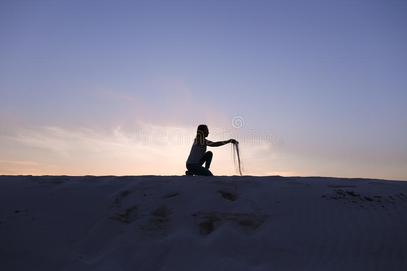 A menina bonita senta-se no agachamento no monte arenoso do deserto no por do sol imagem de stock