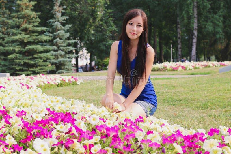 A menina bonita senta-se perto dos canteiros de flores fotografia de stock