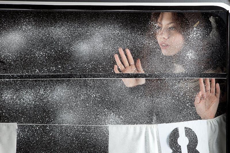 Menina bonita sobre a janela coberto de neve foto de stock royalty free