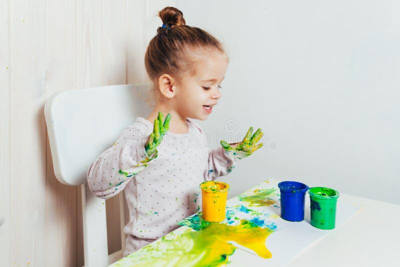 A menina bonita tira com pinturas do dedo em uma folha de papel branca fotografia de stock