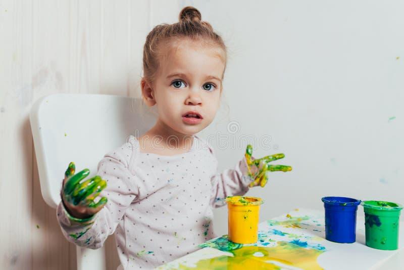 A menina bonita tira com pinturas do dedo em uma folha de papel branca foto de stock royalty free