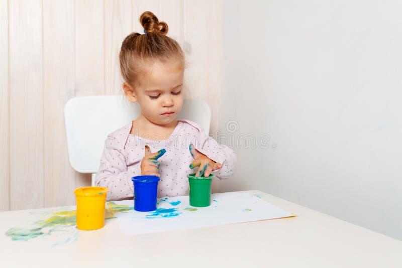 A menina bonita tira com pinturas do dedo em uma folha de papel branca imagens de stock royalty free