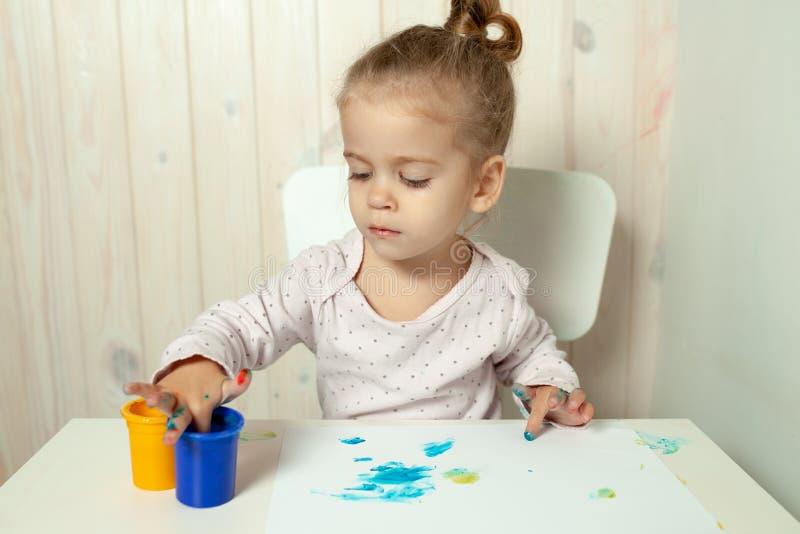 A menina bonita tira com pinturas do dedo em uma folha de papel branca fotos de stock