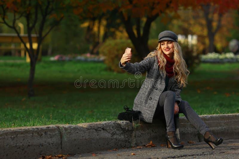 A menina bonita toma um autorretrato com seu telefone esperto no parque do outono imagens de stock royalty free
