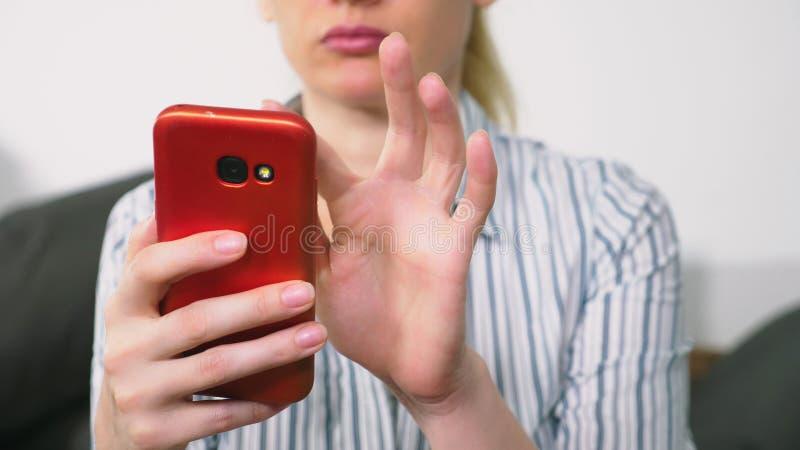 A menina bonita usa um smartphone celular ao sentar-se na sala de visitas na noite Mulher nova de sorriso feliz fotografia de stock royalty free