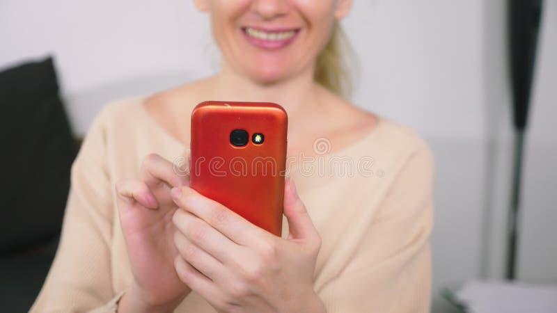 A menina bonita usa um smartphone celular ao sentar-se na sala de visitas na noite Mulher nova de sorriso feliz imagens de stock