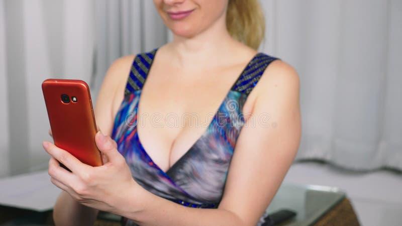 A menina bonita usa um smartphone celular ao sentar-se na sala de visitas na noite Mulher nova de sorriso feliz imagem de stock royalty free