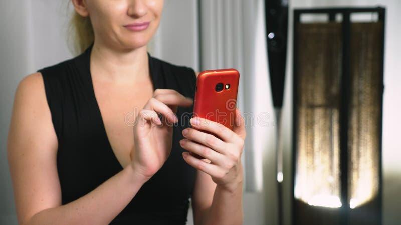 A menina bonita usa um smartphone celular ao sentar-se na sala de visitas na noite Mulher nova de sorriso feliz foto de stock royalty free
