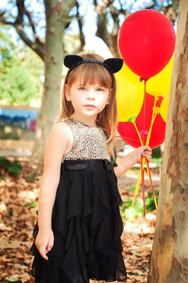 Menina bonita vestida como um gato com os balões nas mãos Sorriso doce, um olhar macio imagem de stock royalty free