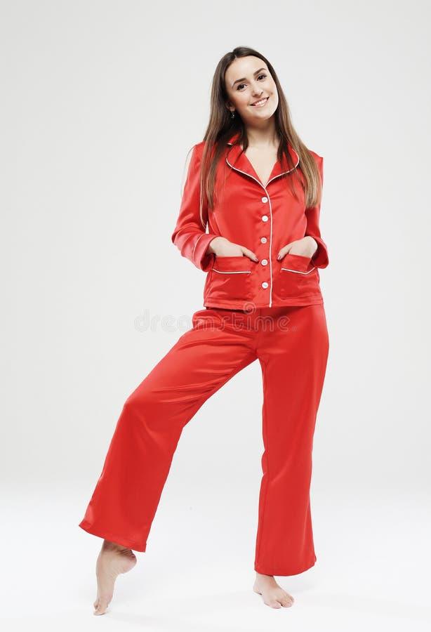 Menina bonita vestida em pijamas vermelhos sobre o fundo branco fotografia de stock royalty free