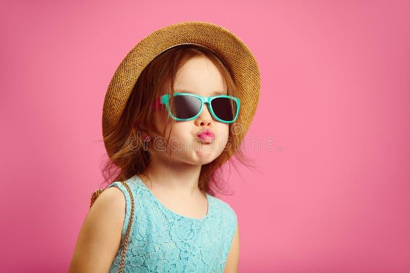 A menina bonita vestida na roupa elegante, veste o chapéu de palha, óculos de sol e o vestido azul, mostra a cara do pato imagens de stock